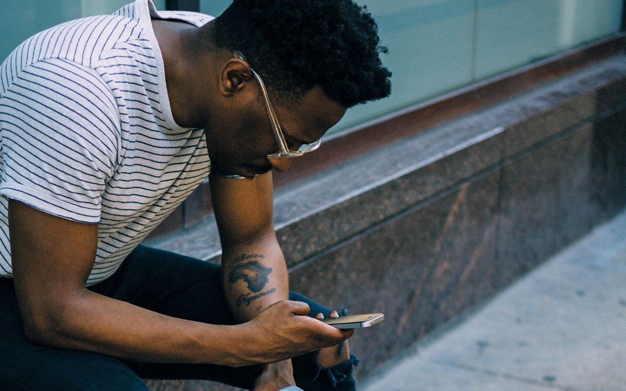 A man sits outside on a wall, he has sunglasses on and a tattoo on his lower left arm. He is holding a phone in his right hand, and looking down at it.