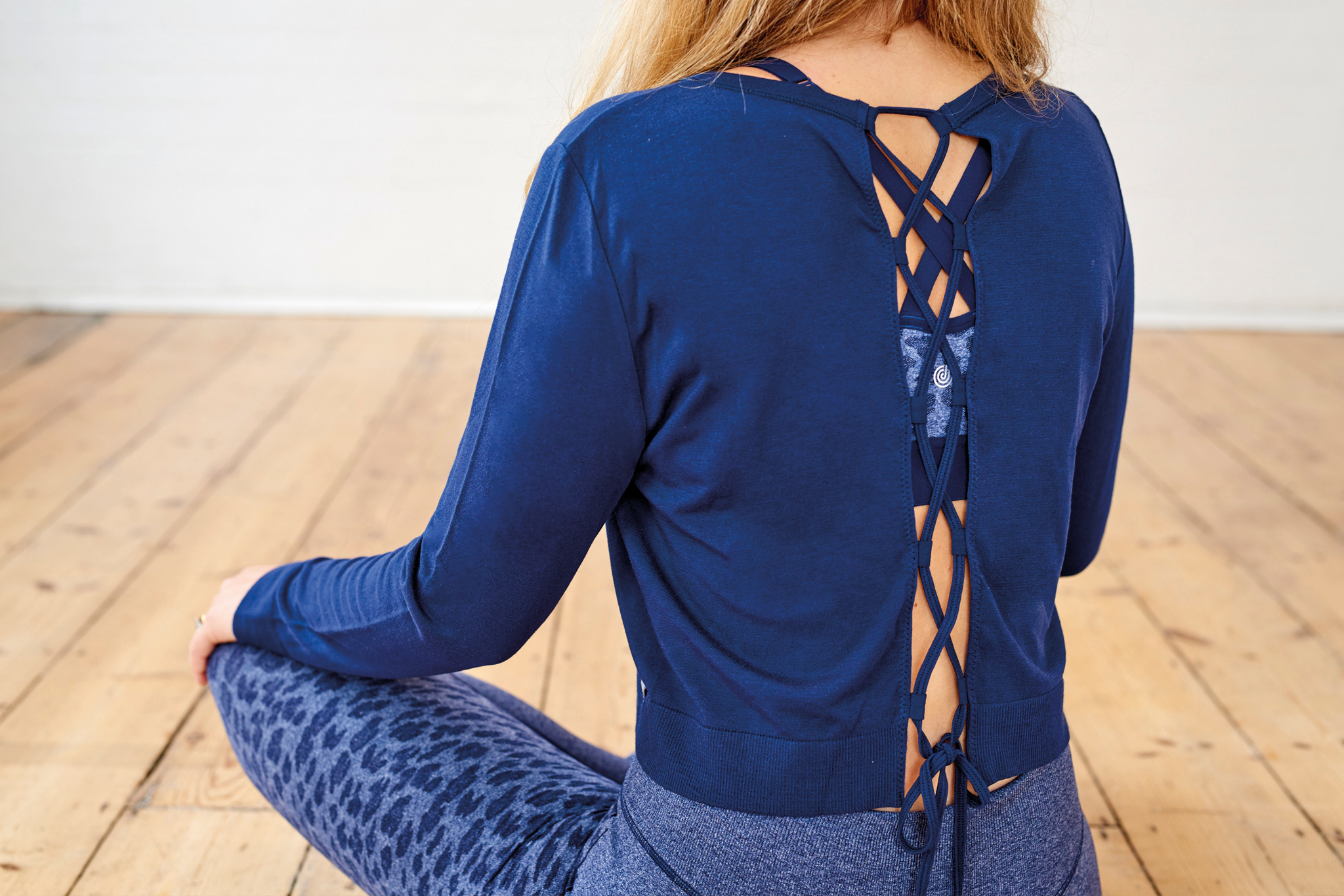 A person sits with their back to the camera, their legs are crossed and their hands are on their knees. They are wearing a blue top that has a criss cross pattern on the back, with blue leggings.