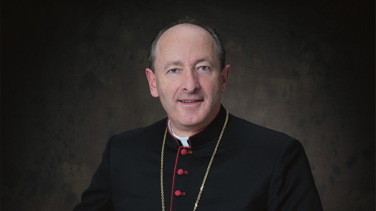 A head-and-shoulders shot of a bishop looking directly at the camera.