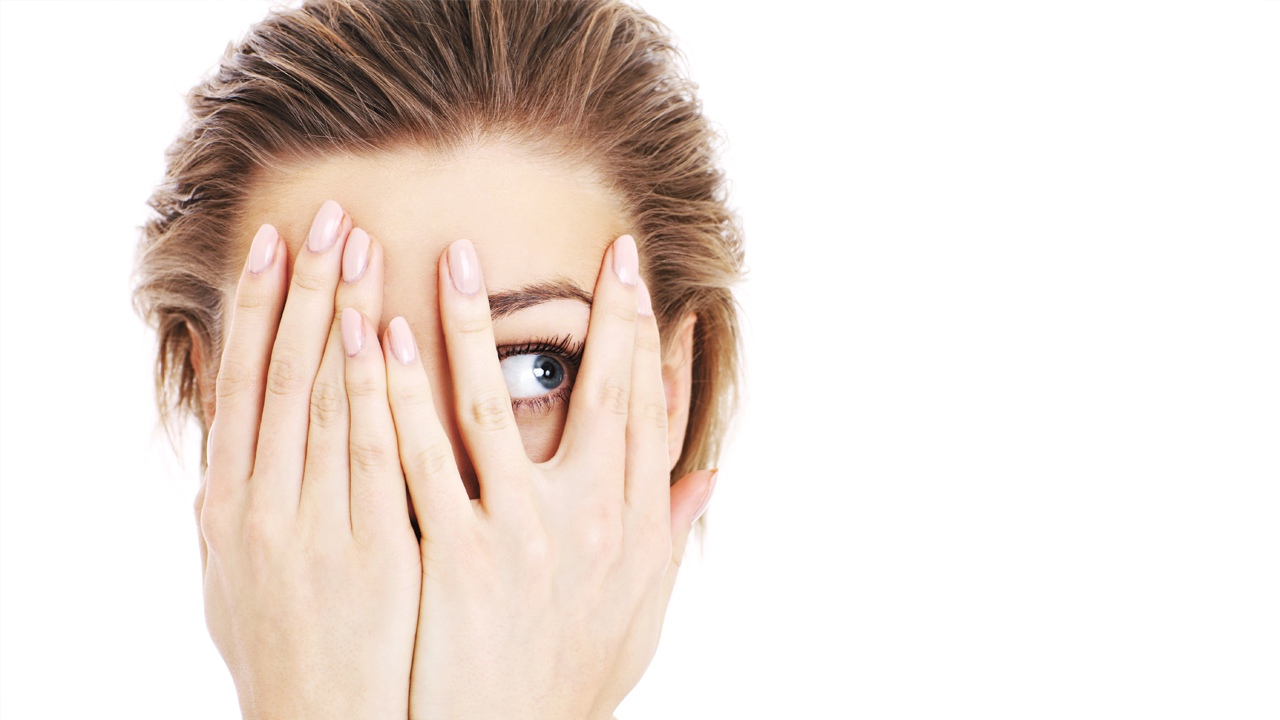 A woman with her hands up to her face; all of her features are hidden except for her right eye which is looking to the left.