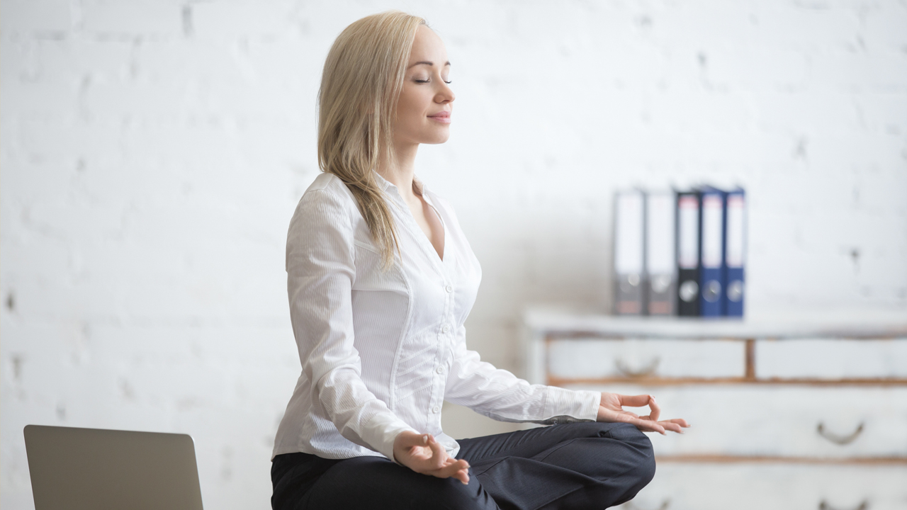 A woman in office wear - a white shirt and dark trouser - is sitting in a meditation pose on a desk with office stuff around her.