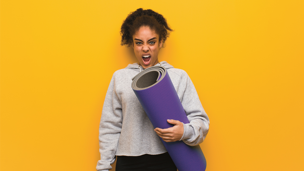 A woman standing against a yellow background: she holds a purple yoga mat and is screaming at the camera.