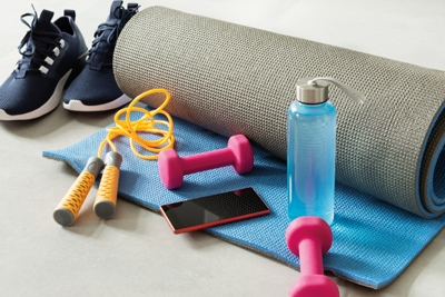 Fitness equipment and smartphone on gray floor background. Training indoors. Home online workout.