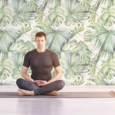 Man sitting at lotus yoga pose. Home morning routine. Teacher fitness studio. Asana class. Online exercise. Relaxation indoor. Male prayer in house room. Light background. Close eyes