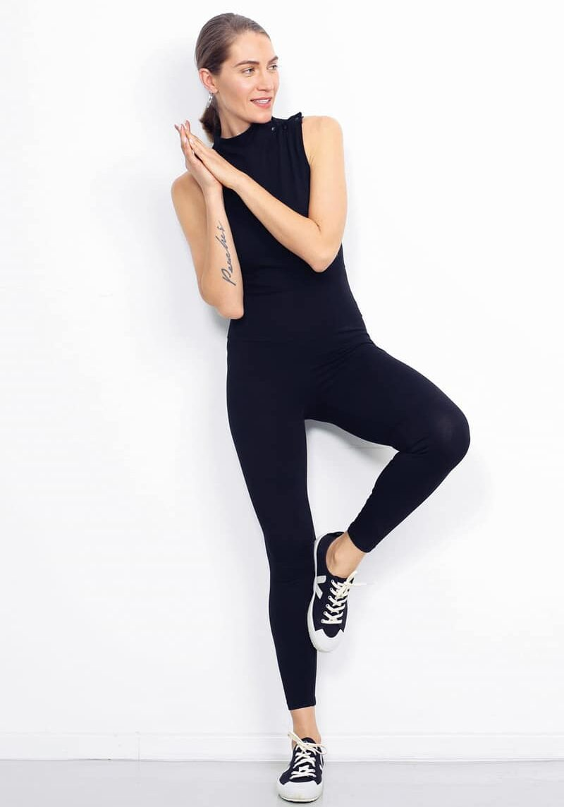 A woman wearing a navy blue turtleneck bodysuit is leaning against a wall with her hands in prayer poisition next to her right shoulder. She has her left leg bent and her left foot is placed against the wall.