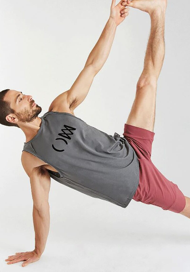 A man is balancing on his right arm and right leg; his left arm is extended into the air and his left hand is clasping his left foot, which is also extended into the air. He is wearing a grey t-shirt and light red shorts.