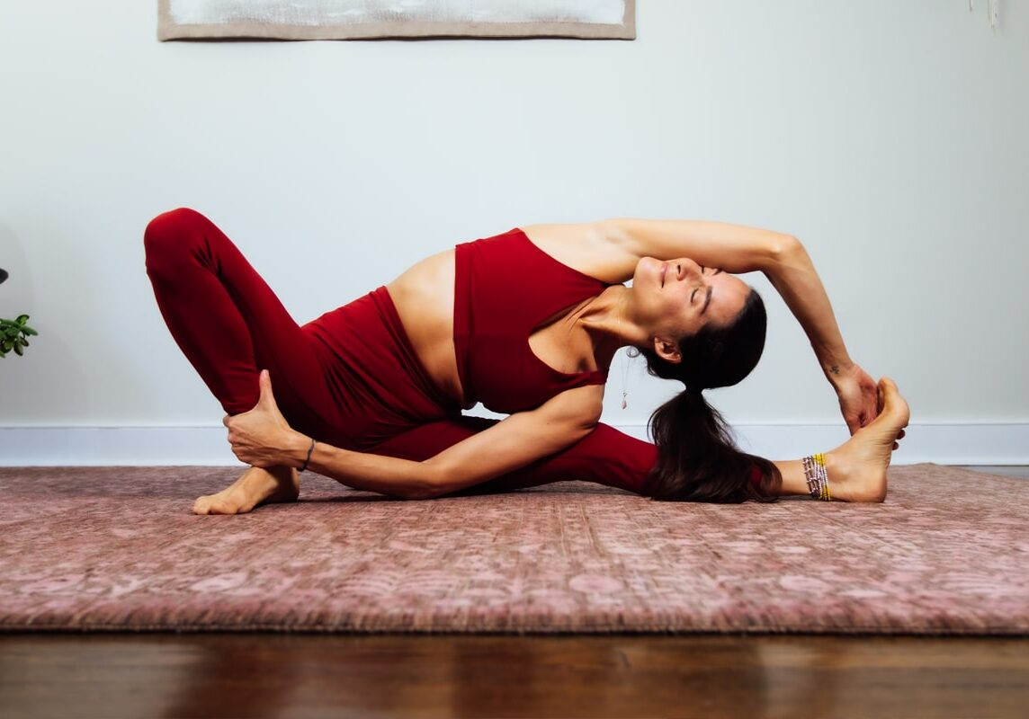 Elena Brower in a yoga pose - she is seated, stretching her body to the left, with her right arm over her head and touching her left foot, with her right leg bent at the knee, her foot on the floor, and her left hand holding her lower right leg.