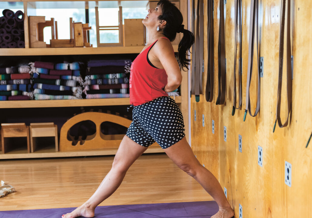 A woman stands on a yoga mat, with her right leg extended to the front, and her back leg extended behind her. She has her hands behind her back.