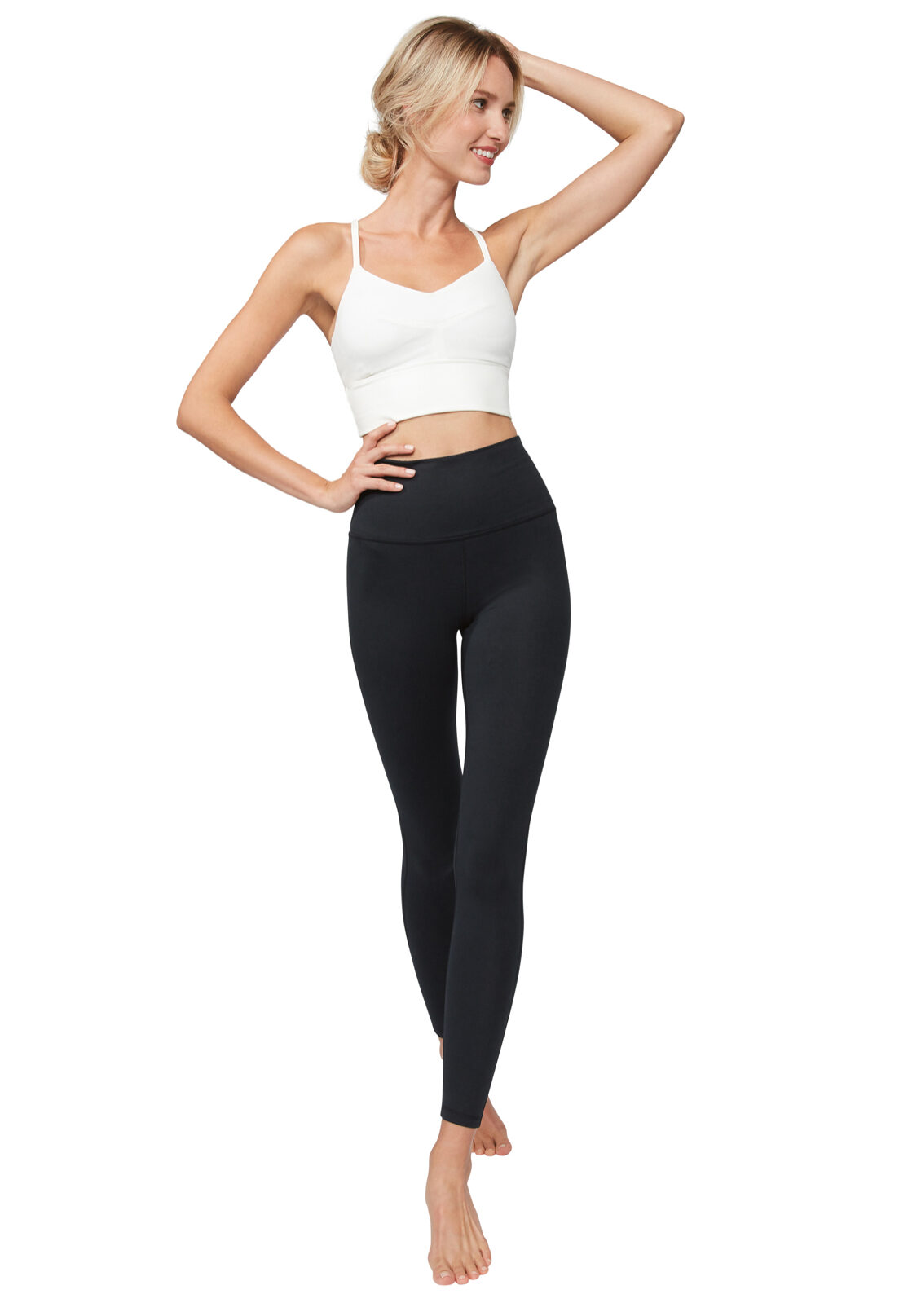 A woman stands with her right hand on her hip, and her left arm bent at the elbow with her hand on her head. Her left foot is slightly in front of her right foot. She is wearing a white cropped top and a pair of black high waisted leggings.