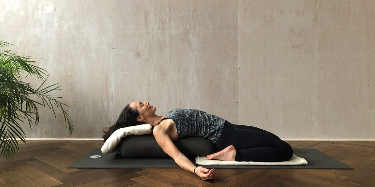 A woman lays on a yoga mat and bolsters with her legs bent beneath her and her arms splayed by her side. She has her eyes closed.