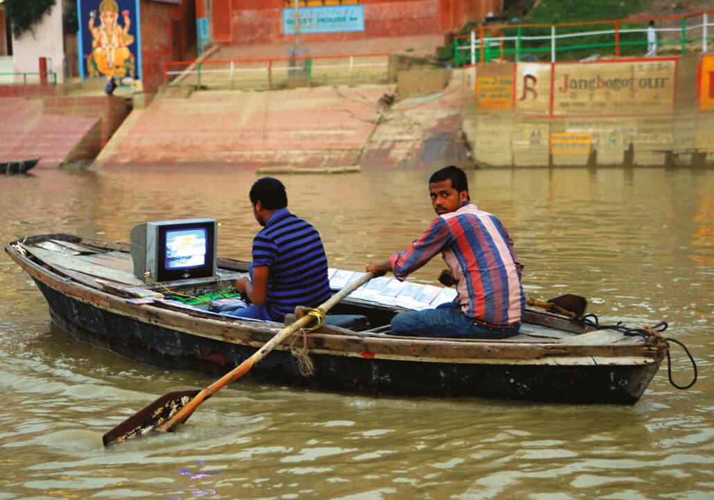 Two men in boat watching television.