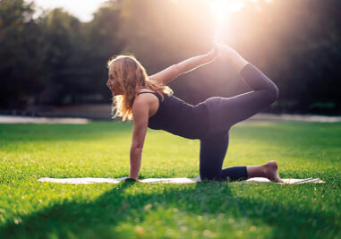 photo in the backlight of female shadow woman doing yoga alone outdoor at the park at sunset